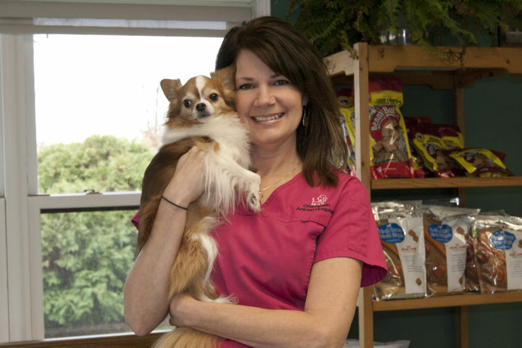 Veterinary manager holding a small brown dog