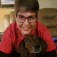 Client care representative hugging a brown dog