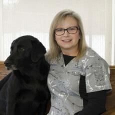 Registered veterinary technician hugging a black dog