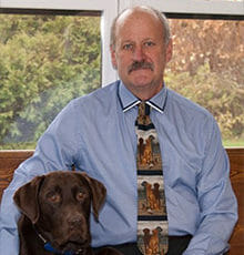 Veterinarian sitting next to large brown dog