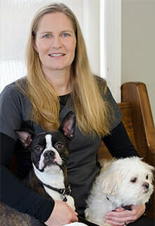 Veterinarian holding a black dog and a white dog